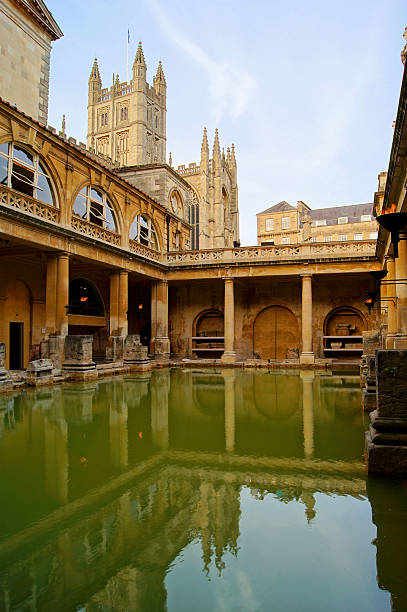Ancient Roman Baths at Bath, England at dusk Ancient Roman Baths at Bath, England at dusk roman baths england stock pictures, royalty-free photos & images