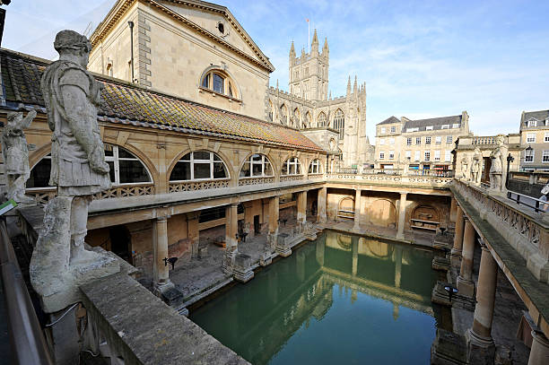 Ancient Roman Baths The Ancient Roman Baths in the English city of Bath - illuminated by afternoon sunshine casting reflections in the thermal bathBath Abbey is visible in the distance framed by the pillars and shadows of the ancient remains belowBritain bath england stock pictures, royalty-free photos & images