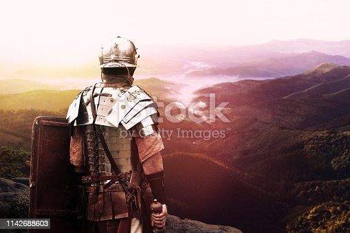 Roman legionary watching the valley at sunset after battle day