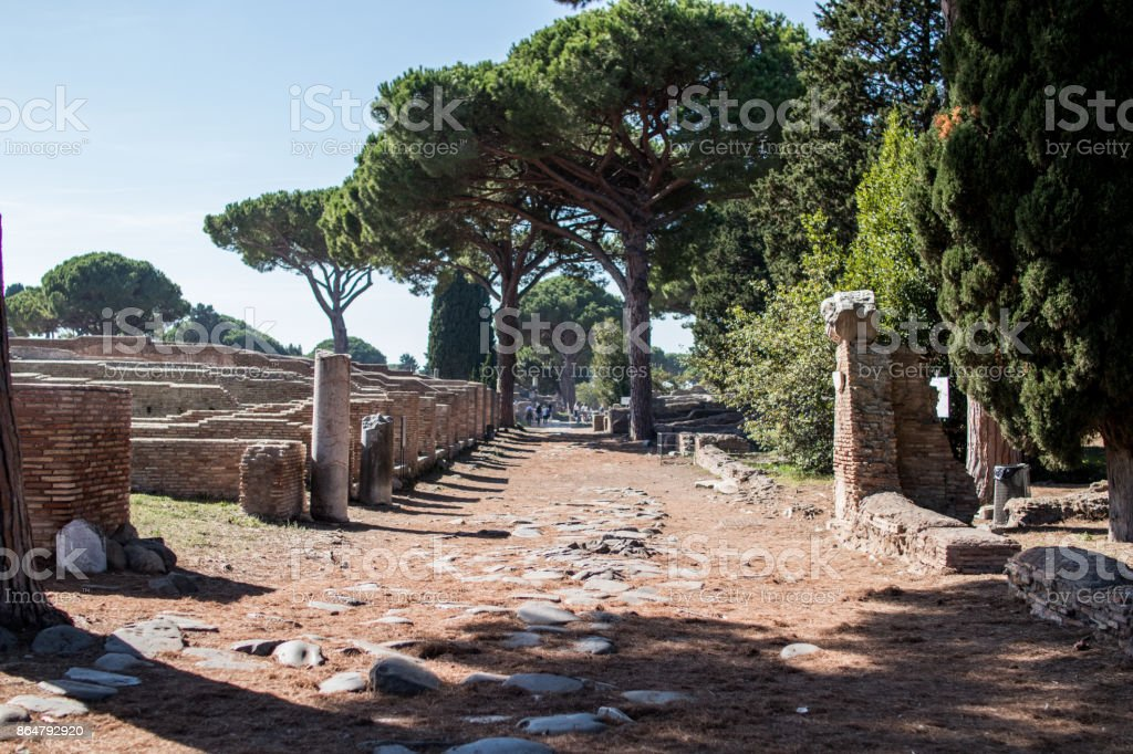 Ancient Rome road in Ostia Antica. View of an ancient ostia road with pines in background stock photo