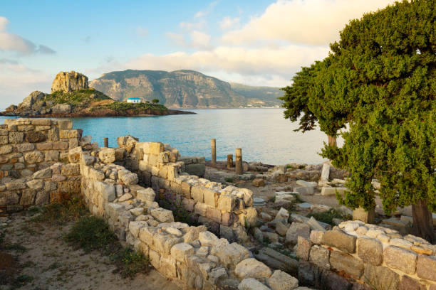 Ancient ruins and small island Kastri with traditional orthodox church in Kefalos bay in Kos island, Greece. stock photo
