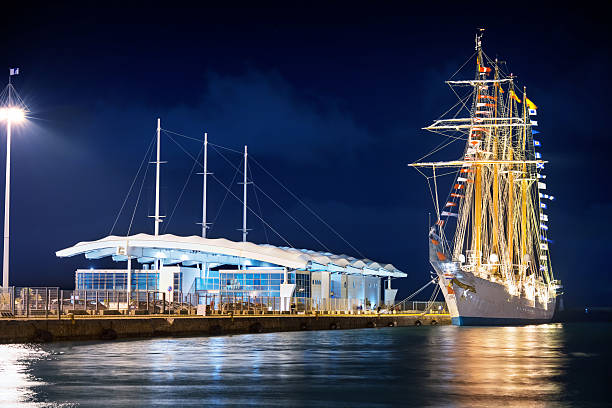 Ancient sailing ship in a modern port stock photo