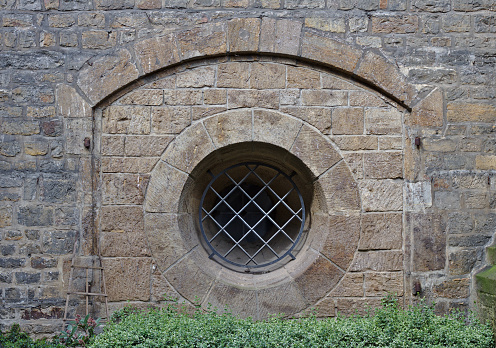 Ancient sandstone wall with arch and barred round window