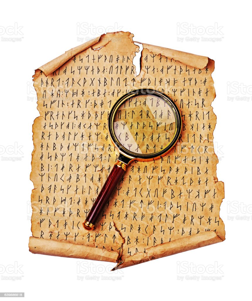 Ancient scroll with the Scandinavian runes and magnifying glass stock photo