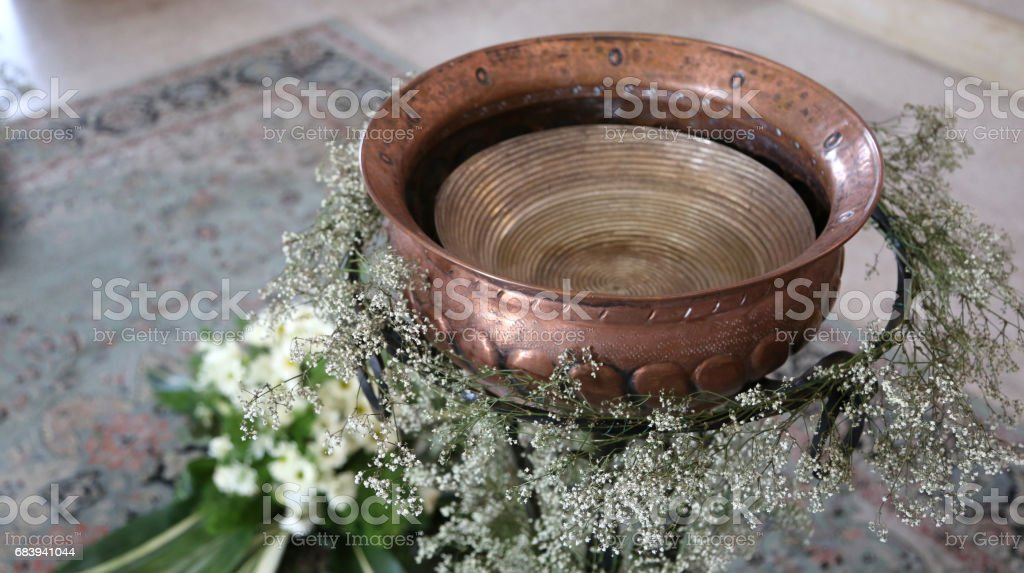 Ancient Small baptismal font in copper decorated with flowers du stock photo