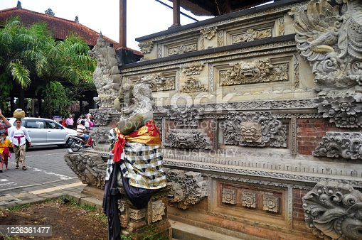 Ancient statue bali style and lifestyle of Balinese people walking on street near Goa Gajah temple or Elephant Cave at Ubud city on March 24, 2018 in Bali, Indonesia
