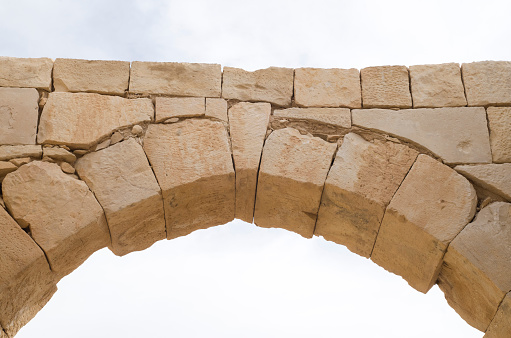 Ancient stone arch and keystone in the sky closeup