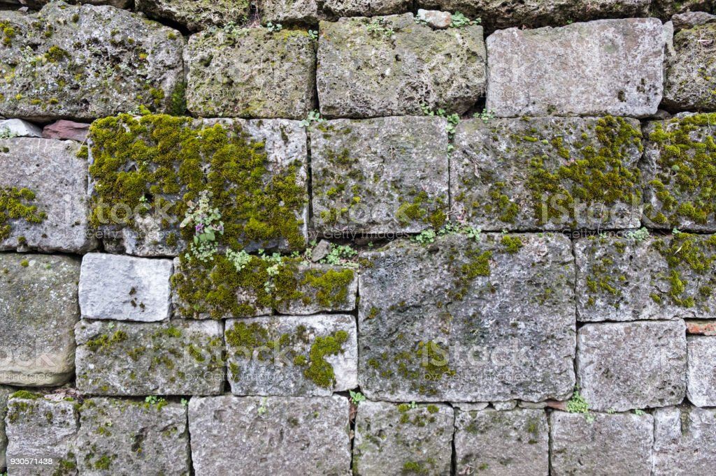 Ancient stone blocks forming rustic wall background with moss gathered on the surface stock photo