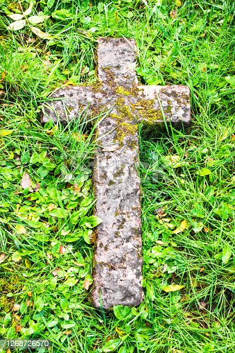 Moss growing on an ancient stone cross, surrounded by grass in a Scottish burial ground.