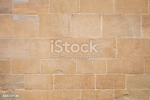 Ancient stone wall of a Romanesque cloister.