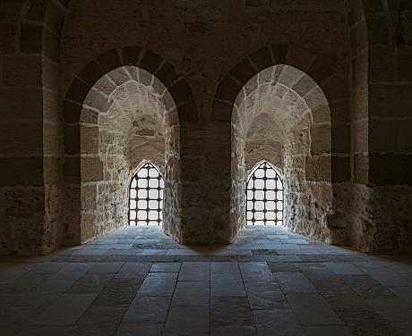 Ancient stone wall with two adjacent backlit windows, Qaitbay Castle