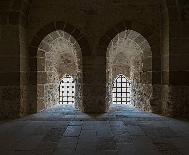 Ancient stone wall with two adjacent backlit windows, Qaitbay Castle stock photo