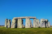 Ancient Stonehenge on Salisbury Plain in the UK with a few tourists inside and around against a very blue sky