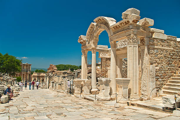 ancient temple ruins with tourists walking around Izmir, Turkey - May 14, 2015: Hadrian's temple ruins with tourists walking around in anceint city of Ephesus on sunny day celsus library stock pictures, royalty-free photos & images