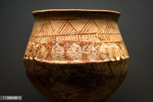 Ancient terracotta pot from the excavations in Greece. Painted archeological pottery. Remains of Ancient Greek culture. Antique ceramic with ornament. Old Greek patterned pottery on dark background.