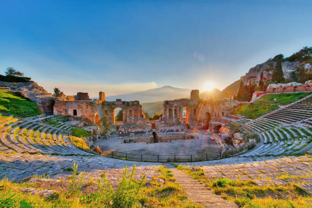 Ancient theatre of Taormina with Etna erupting volcano at sunset Ancient theatre of Taormina Siciliy Italy  with Etna erupting volcano at sunset sicily stock pictures, royalty-free photos & images