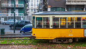 Milan, Italy - Apr 23, 2013: Ancient tram moving on street under the rain
