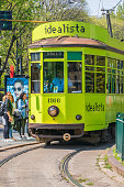 Milan, Italy - Apr 17, 2019: Ancient tram with tourists near station