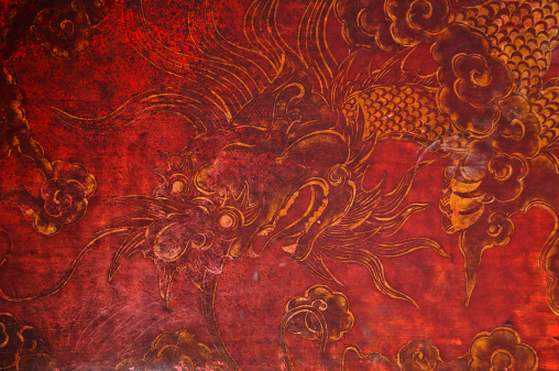istock Ancient vintage golden painting of dragon on red wooden wall 488025913