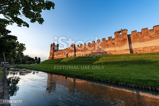 Castelfranco Veneto, Italy - June 1th, 2014: the ancient medieval walls of Castelfranco Veneto town at sunset (XII-XIII century) with the moat full of water and the embankment. Treviso province, Italy, Europe