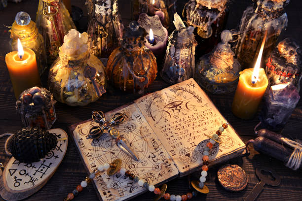 Ancient witch book with magic spell, black candles and decorated bottles. stock photo