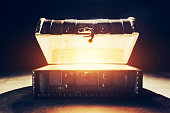 istock Ancient wooden box with glowing light. 1126694541