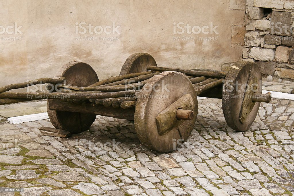 Ancient wooden cart on cobblestone path stock photo