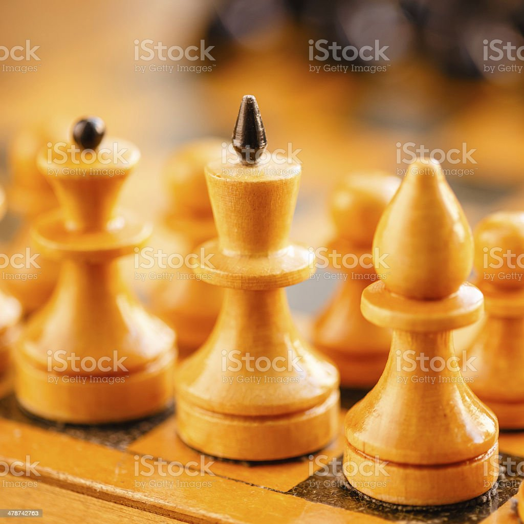 Ancient wooden chess standing on chessboard royalty-free stock photo