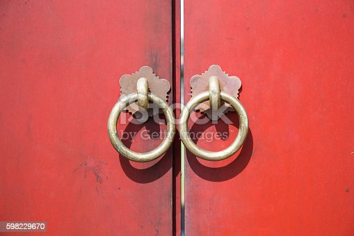 istock Ancient wooden gate with two door knocker rings 598229670