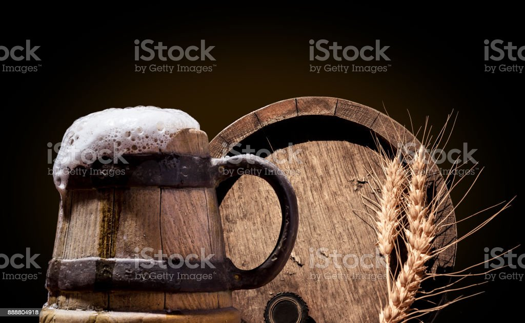 Ancient wooden pint with beer on dark background. stock photo