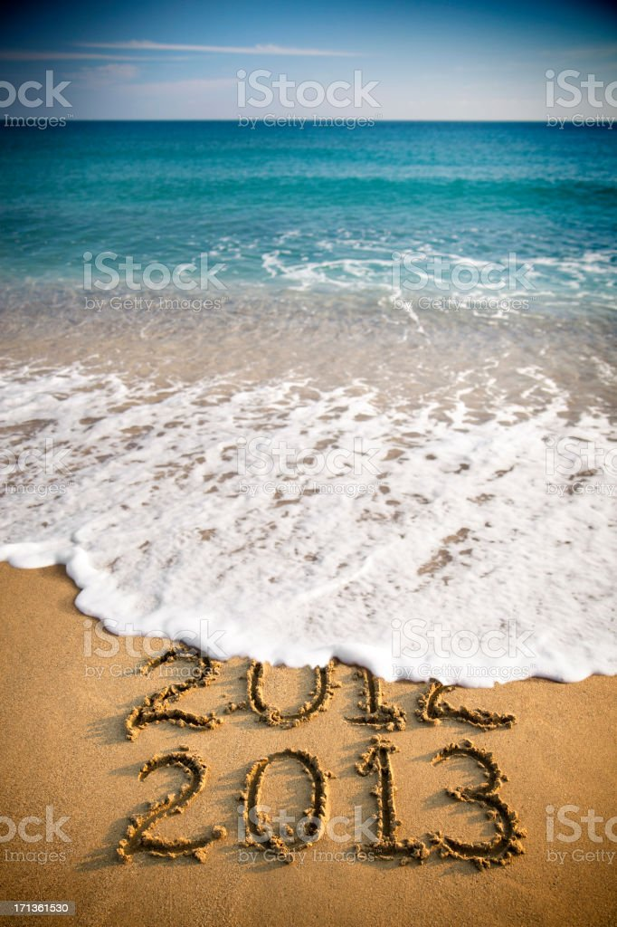 2013 and 2012 written in sand with waves royalty-free stock photo