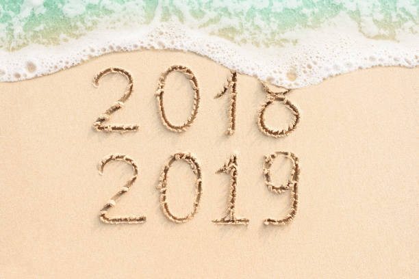 2018 and 2019 written on the beach stock photo