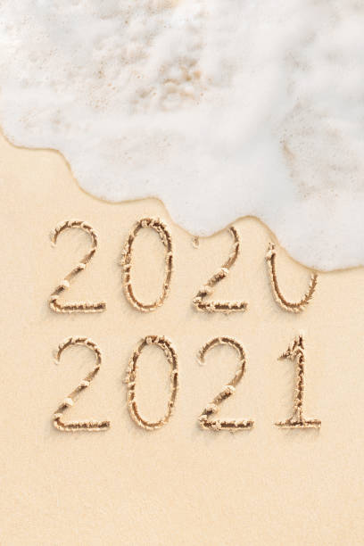 2021 and 2020 handwritten on the sand stock photo