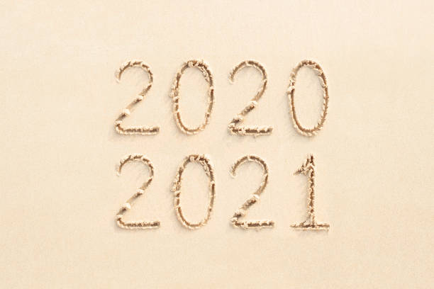 2021 and 2020 numbers written on sand stock photo