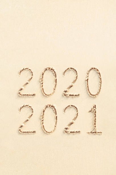 2021 and 2020 numbers written on sandy beach stock photo
