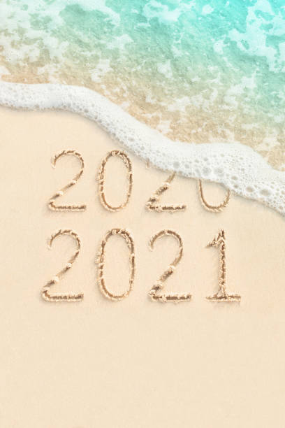 2021 and 2021 on the beach with ocean wave stock photo