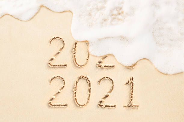 2020 and 2021 written on sandy beach background stock photo