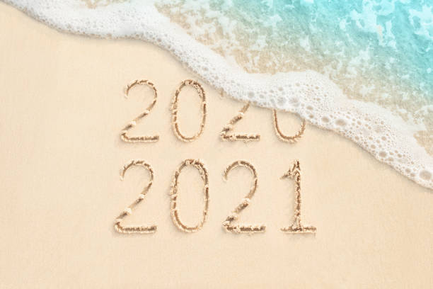 2021 and 2021 written on the beach background stock photo