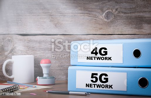 istock 5G and 4G network. Two binders on desk 1165461788