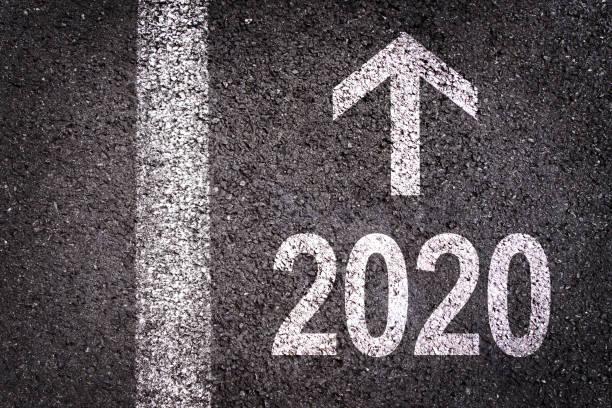 2020 und ein Richtungspfeil auf einem Asphaltstraßenhintergrund geschrieben, urbane Neujahrsgrußkarte – Foto