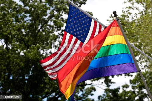 Rainbow and American flags in the wind flying proudly together. Image shot with Canon 5D Mark 4, EF 70-200mm f/2.8L lens.