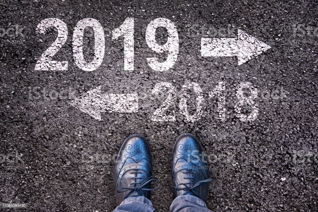 2019 and an arrow written on an asphalt road background with legs stock photo