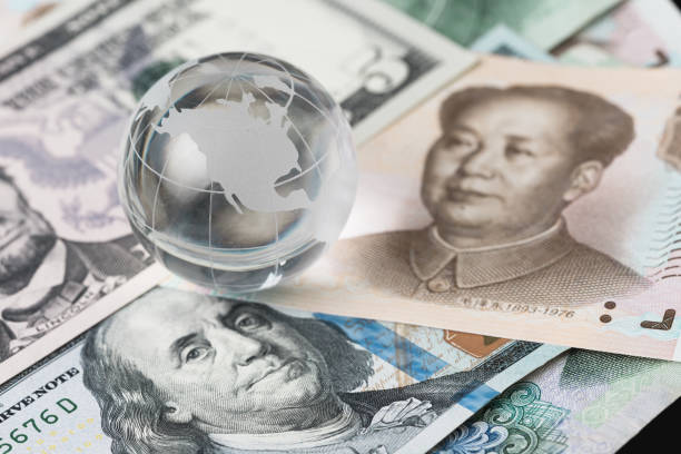 US and China trade barrier, an action by a government that makes trade between the country and other countries more difficult, decoraton glass globe on US dollar and china yuan banknotes - foto stock