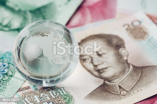 istock US and China trade war, tariff, tax barrier, decoraton glass globe with the side of United States map on China yuan banknotes 944415074