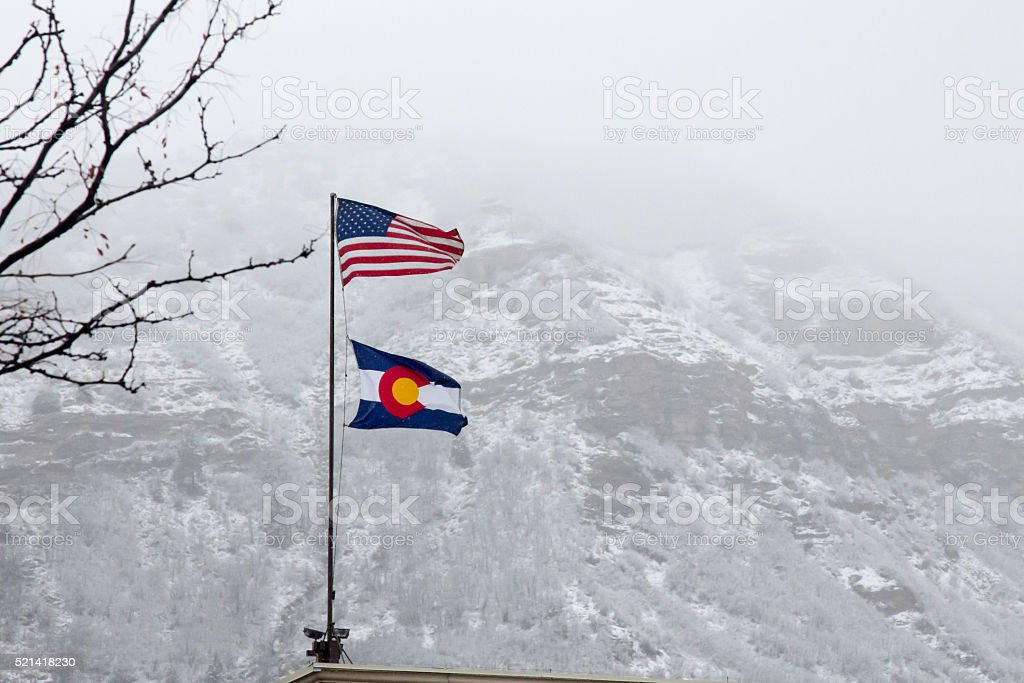 USA and CO Flags against a snowy foggy hillside stock photo