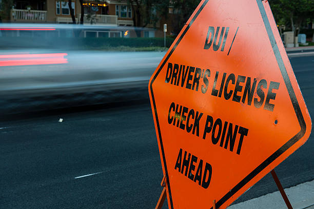 DUI and Driver License Checkpoint motion DUI (sobriety) / Driver's License Checkpoint Ahead sign on side of roadway with cars in motion in background approaching checkpoint security barrier stock pictures, royalty-free photos & images