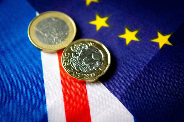 UK and Euro flags The flag of the EU on top of a larger Union Flag representing Britain.  There are new one pound coins and old Euro coins on the flags. british currency stock pictures, royalty-free photos & images