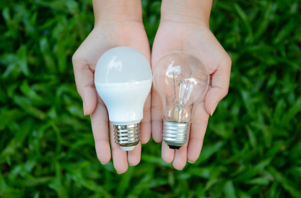 LED and Fluorescent bulb comparing on woman hand for alternative technology concept LED and Fluorescent bulb comparing on woman hand for alternative technology concept canadian football league stock pictures, royalty-free photos & images