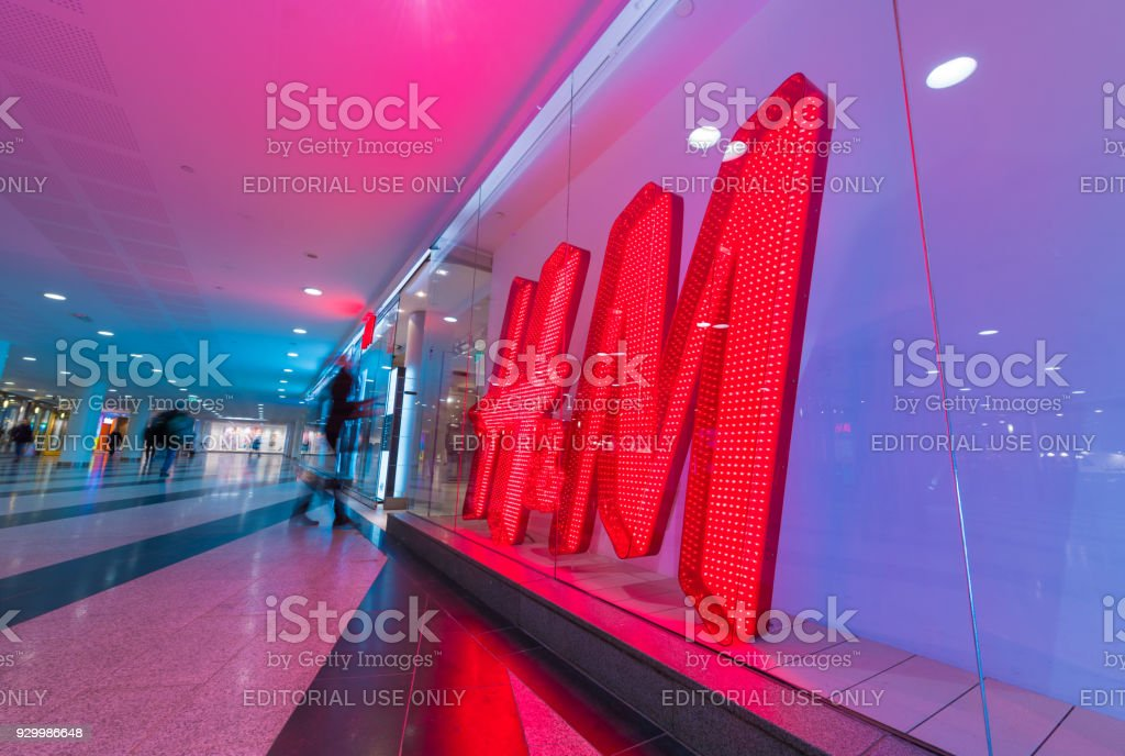 HM  H and H H&M sign and motion blurred shopper - foto stock