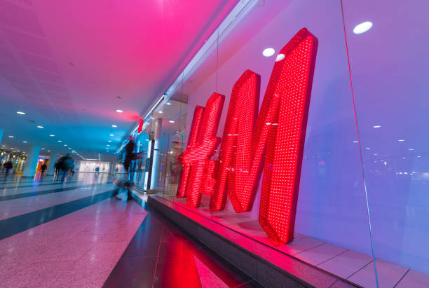 HM  H and H H&M sign and motion blurred shopper stock photo